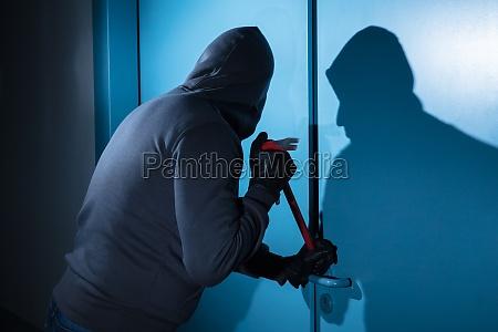 zlodziej probujacy zlamac drzwi