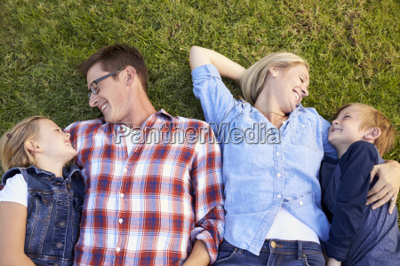 young white family lying on grass