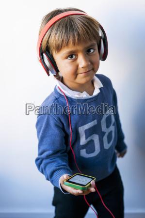 maly chlopak slucha muzyki swojego smartfona