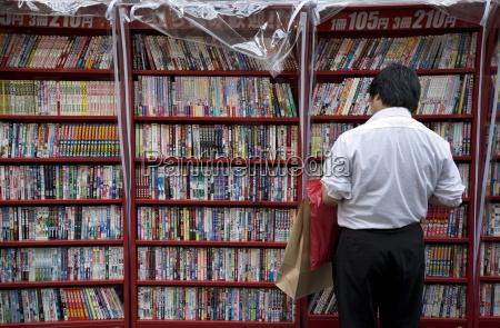 mezczyzna przegladania japonskich komiksow manga w