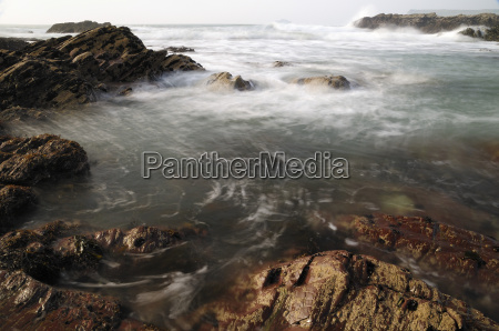 sea swirling around rocks near polzeath