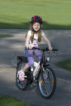 austria girl riding bicycle on asphaltroad