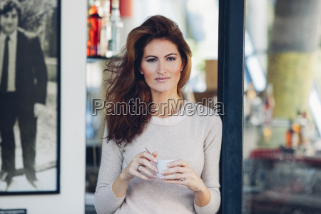 smiling woman outdoors holding cup of