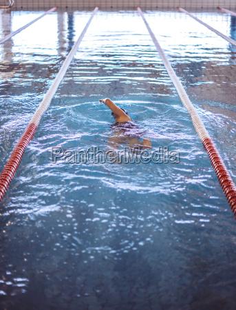 zenska plywaczka w krytym basenie
