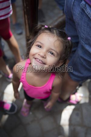 portret usmiechnietej dziewczynki stojacej miedzy doroslymi