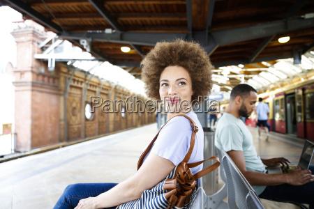 mloda kobieta siedzi na lawce na