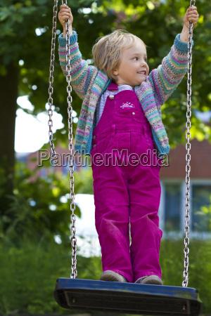 germany kiel girl standing on swing