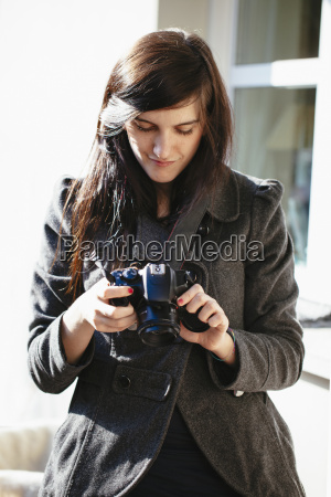 mloda kobieta patrzy na jej aparat