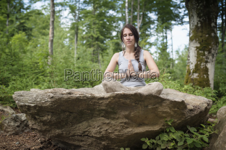 kobieta siedzaca na skale w medytacji