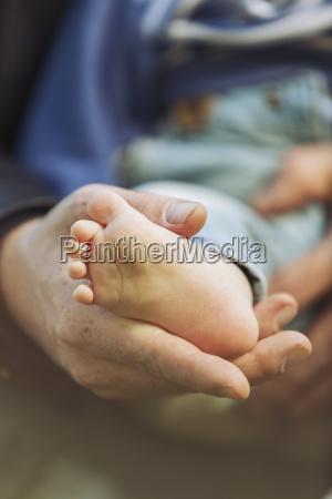 ojciec trzyma stope swego malego syna