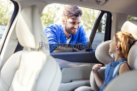 ojciec stojacy na oknie samochodu rozmawiajac
