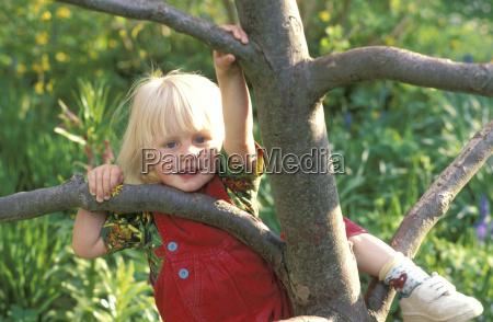 girl climbing on tree portrait