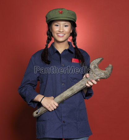 young woman standing with spanner smiling