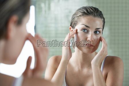 kobieta badajaca sie przed lustrem