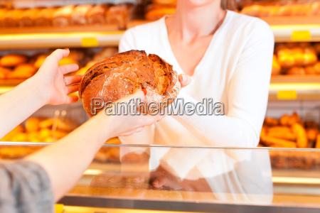 sprzedawca z klientem w piekarni