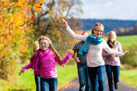 rodzina spacer jesienia las flying kite