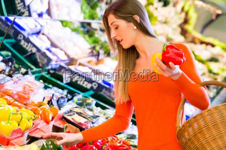 kobieta wybierajaca warzywa w sklepie spozywczym