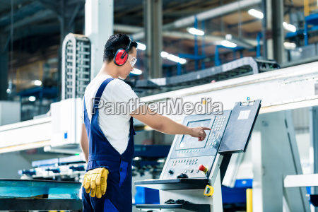 pracownik wprowadzanie danych w maszynie cnc