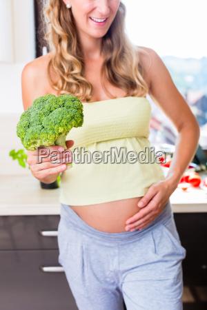 kobieta w ciazy zdrowa pokazuje warzywa