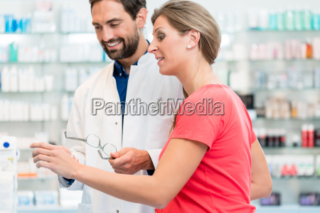 women being helped by pharmacist to