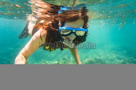 kobieta snorkeling na pietrze morza tropikalnego
