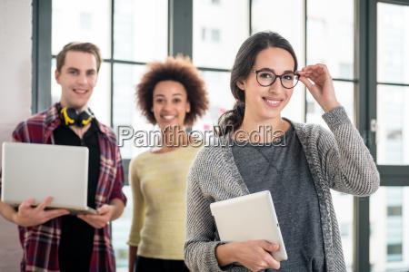 portret mlodego czlowieka usmiechniety trzymajac laptopa