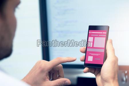 programowanie aplikacji mobilnych programista ze smartfonem