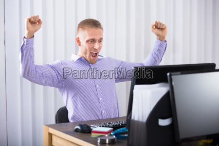 businessman raising his hands in office