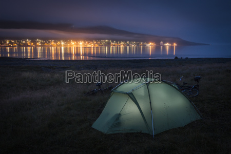 tent on grassy beach illuminated from