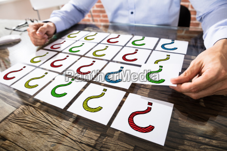 businessman holding question mark on adhesive