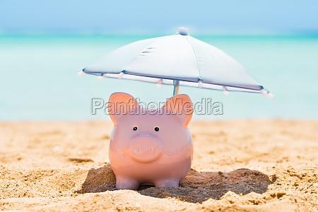 piggy bank pod parasolem na plazy