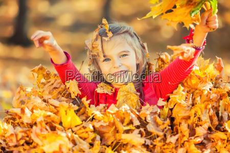 happy little girl gra z jesiennymi