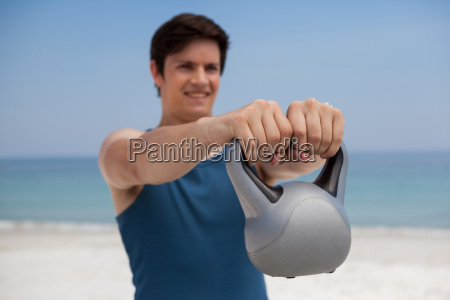 young man holding kettlebell at beach