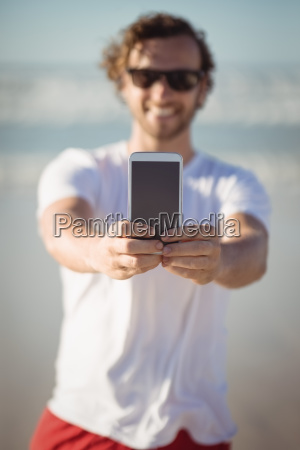 smiling man holding mobile phone at