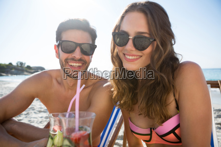 portrait of smiling couple holding drinks