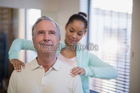 young female therapist giving shoulder massage