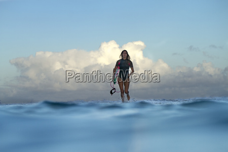 female surfer walking in water and