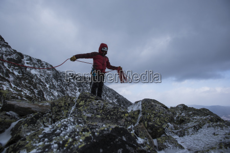climber holding rope while standing against