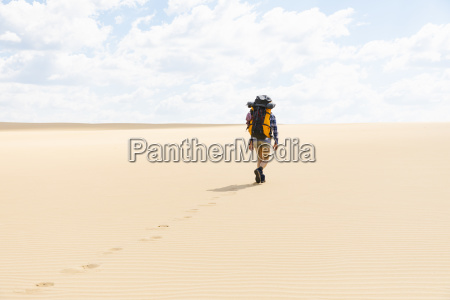 woman hiking on sandy beach in