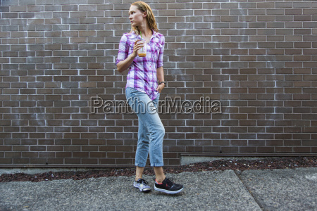 young woman walking down sidewalk with