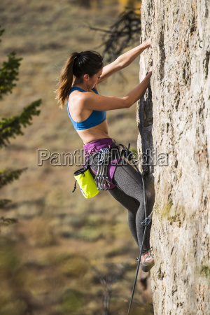 side view of female climber climbing
