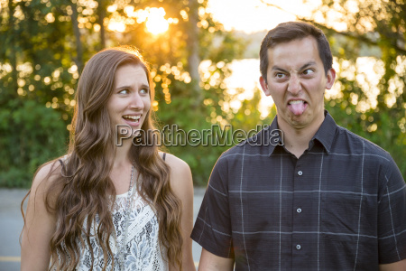 man pulling funny face and woman