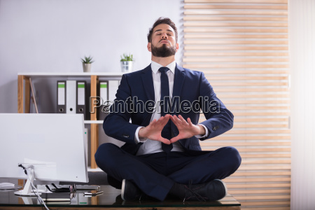 businessman doing yoga in office