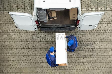 dwoch kurierow rozladunku mebli z pojazdu