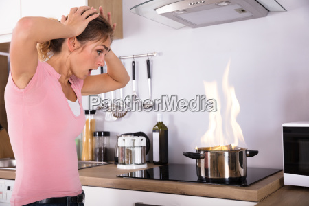 wstrzasniety mlody kobieta patrzac w gotowanie