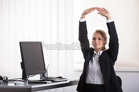 businesswoman siedzacy na krzeslo rozciaganie jej