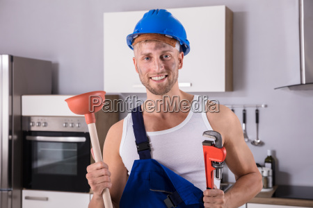 young plumber holding wrench and plunger