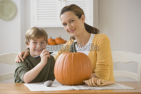 mother and son decorating pumpkin