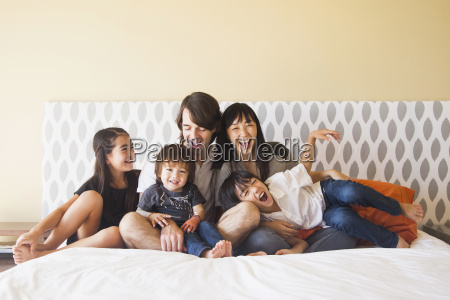 portrait of family sitting on bed