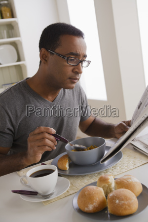 mature man eating breakfast and reading
